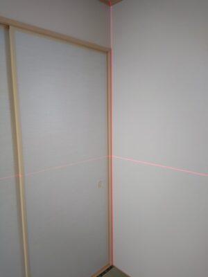 赤外線レベラーを使用して水平と垂直を測定します。